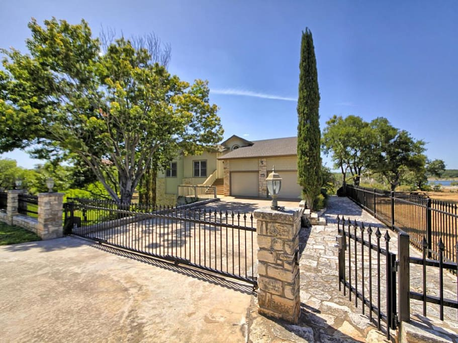 Front of house with Gated driveway and gated access to the estate grounds.  Entire yard is gated all the way around entire house with gorgeous wrought iron fencing.  Perfect to lock the kiddos and pets in.