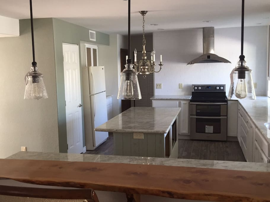 Completely renovated kitchen w/granite countertops, double oven, juniper wood bar, subway tile, coffee station, stainless steel sink & more.