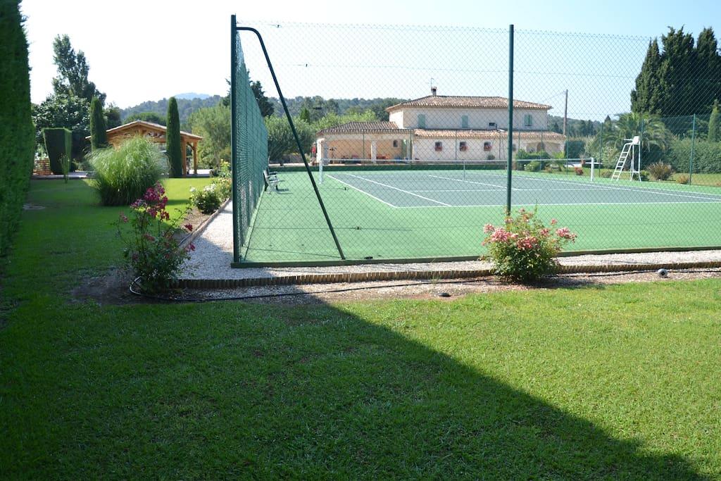 La photo, prise au bout du jardin de derrière, montre le terrain de tennis et l'arrière de la maison.