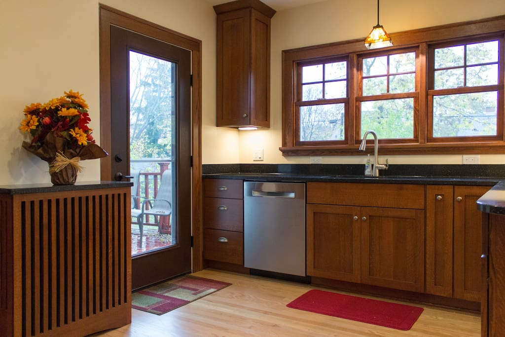 Windows overlook the backyard and a door to the back deck with gas grill.
