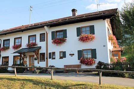 Holiday home in the Allgäu featuring a tiled stove and a private terrace with mountain views.