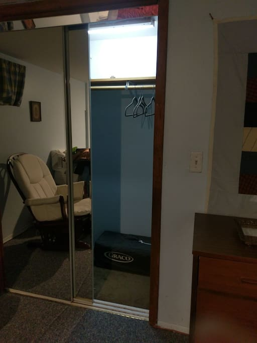 roomy closet with light, mirrored sliding closet doors, pack n play, rocking chair