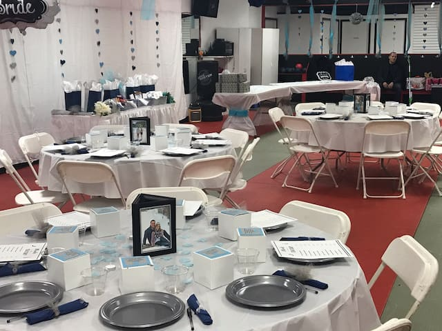 We have several traditional rectangular banquet tables and plastic chairs available.  Additional tables including round ones and other chairs are available from a local rental.  We could pick them up for you if you desire.
