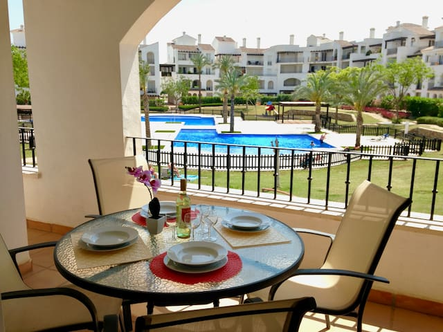 Spacious balcony with a large dining table with 4 chairs, 2 sun loungers and 2 beach chairs