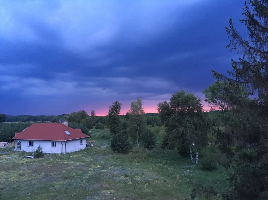 The view from the rooftop of the main house towards the small house, where the landlord lives, just before the summer storm.