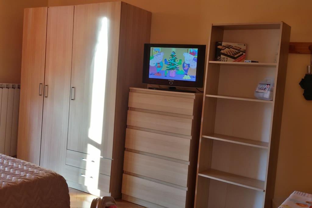 Ampi armadi davanti al letto con scaffaletti e giochi a disposizione degli ospiti