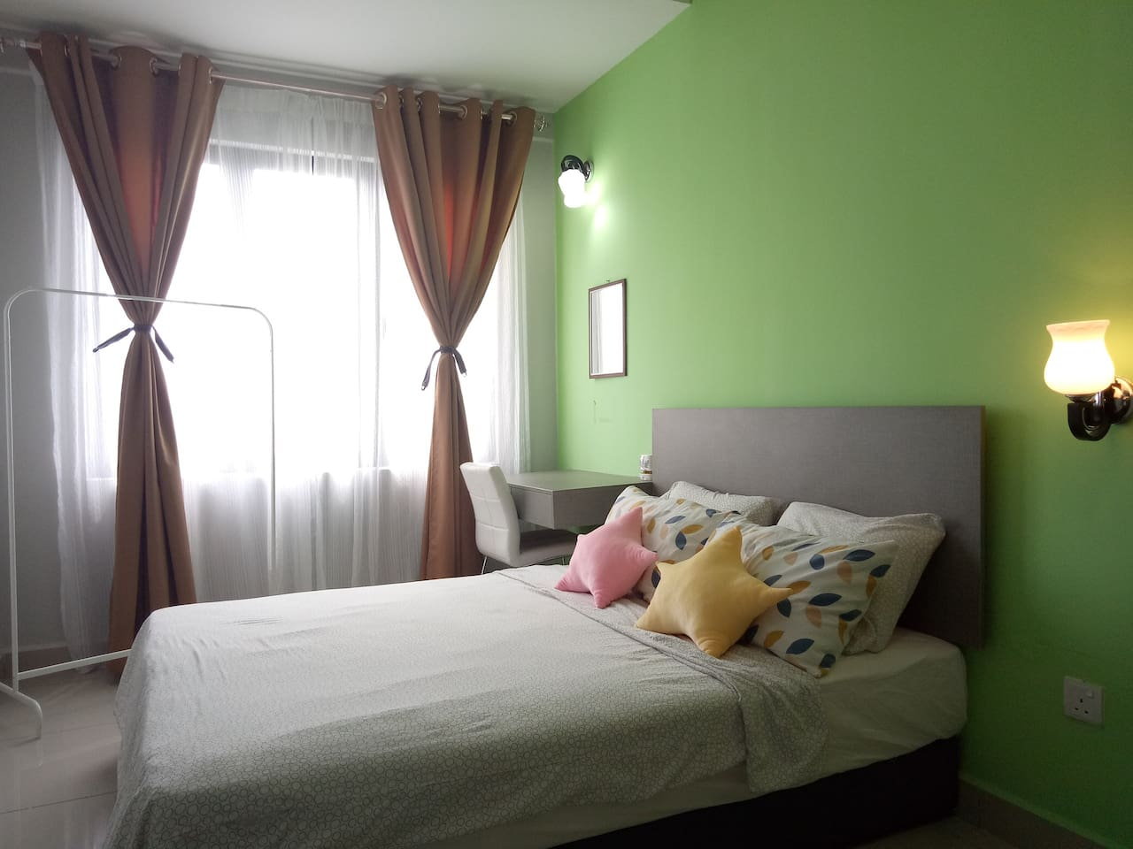 Master bedroom with Queen-sized bed, comforter, air-conditioner, black-out curtains, bed-side lamp and dressing table for you to relax comfortably