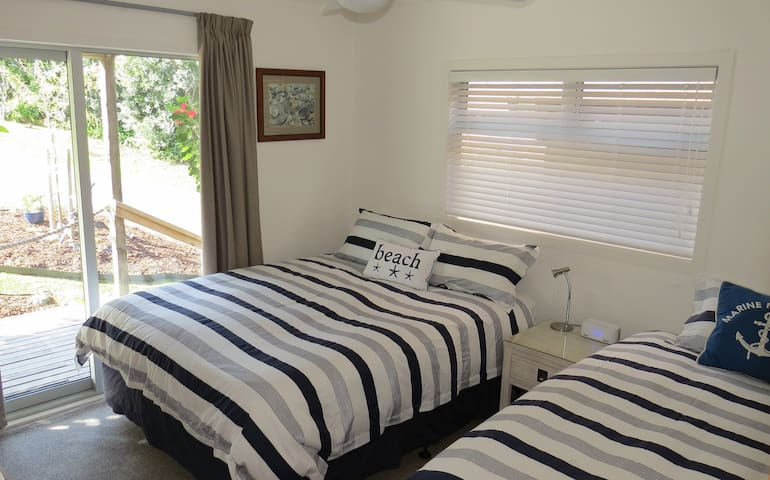 Side bedroom - new queen and king single beds, BT clock radio, ceiling fan, outdoor access