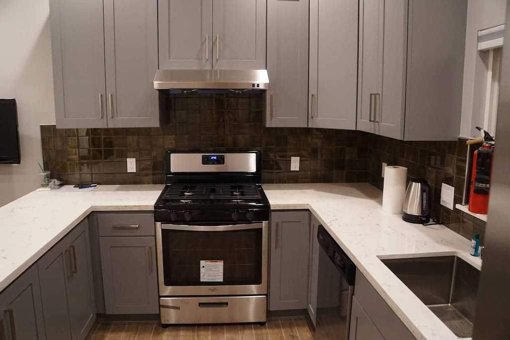 New kitchen has microwave, water boiler, full stove, oven and fully stocked eating and cooking utensils