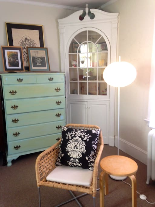 Sitting area and antique cabinet in bedroom.