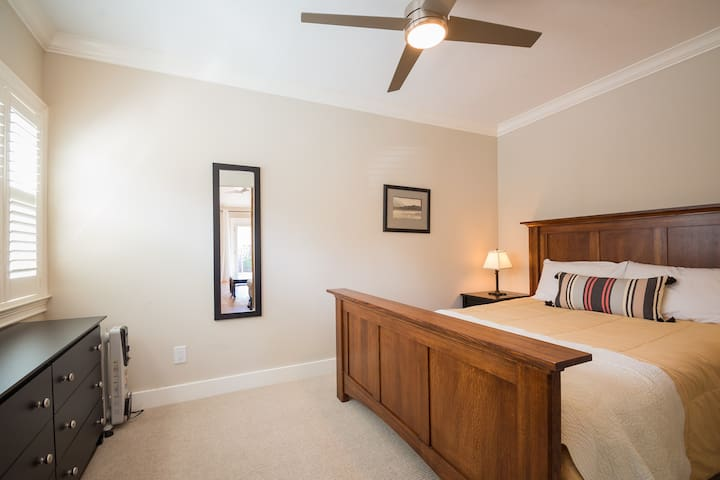 The bedroom features a Restoration Hardware queen-sized bed, with four hypo-allergenic pillows and comforter, two nightstands with reading lamps, a six-drawer dresser, full length mirror. There is also a ceiling light and fan.