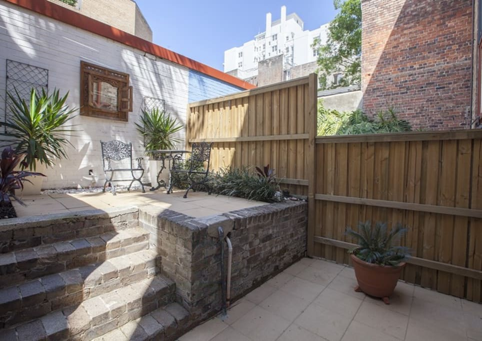 Sunny outdoor area with BBQ and dining area.