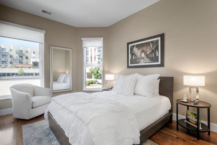 Luxurious bedroom featuring queen-sized bed, hotel-pressed linens and Detroit inspired artwork