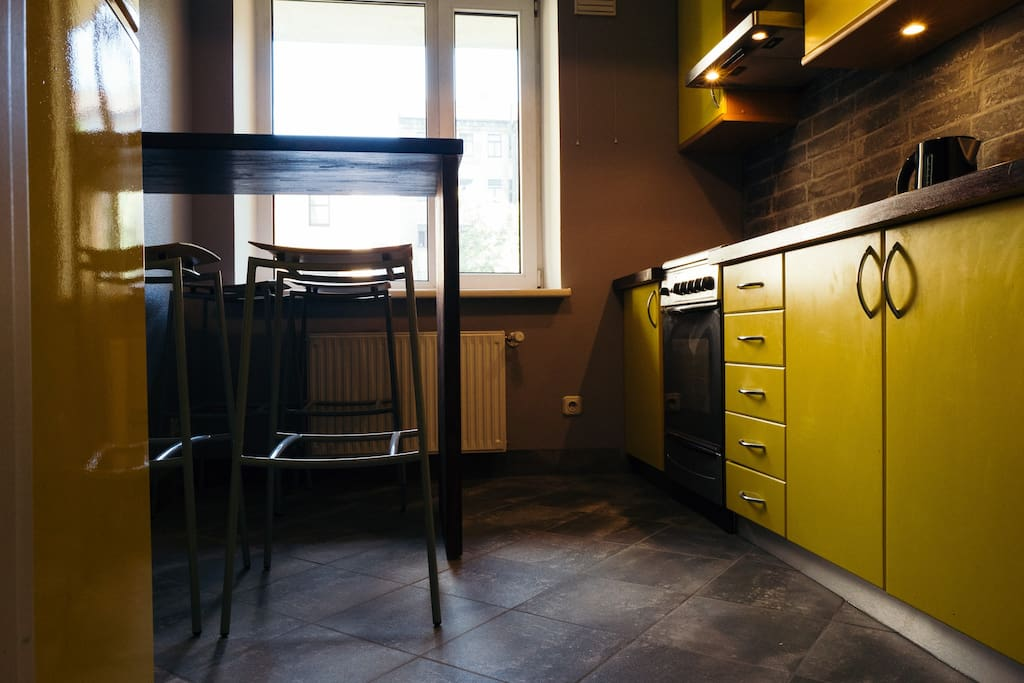 Kitchen with oven, gaz cooker, table bar, kettle, fridge.