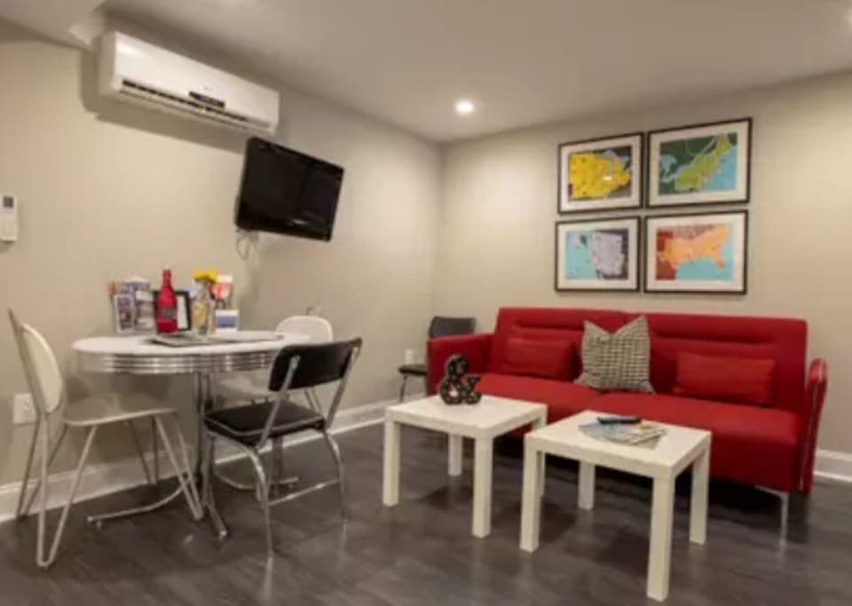 Living/Kitchen area has a Mid-Century style couch that converts to a twin+ bed, a flat screen Apple TV mounted on the wall, air conditioning/heating unit to control temperature and a full kitchen with table for four to five people.