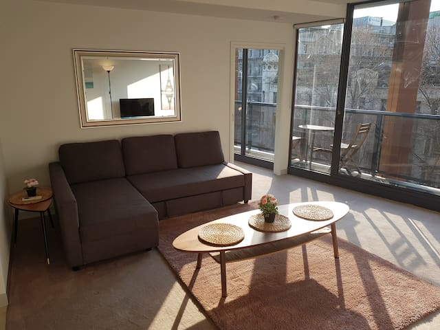 Spacious lounge area with balcony access and city views