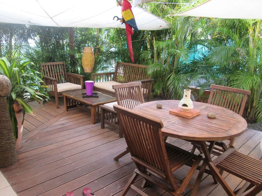 Espace terrasse sur deck avec coin salon et repas.
