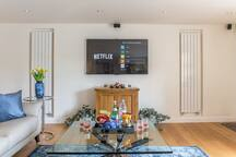 "60"" HDTV w/ 5 ceiling speakers for SURROUND SOUND effect.  Apple TV.  NETFLIX enabled."