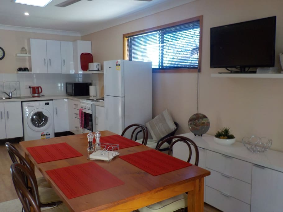 A modern open plan fully  equipped kitchen with full sized fridge & a washing machine.