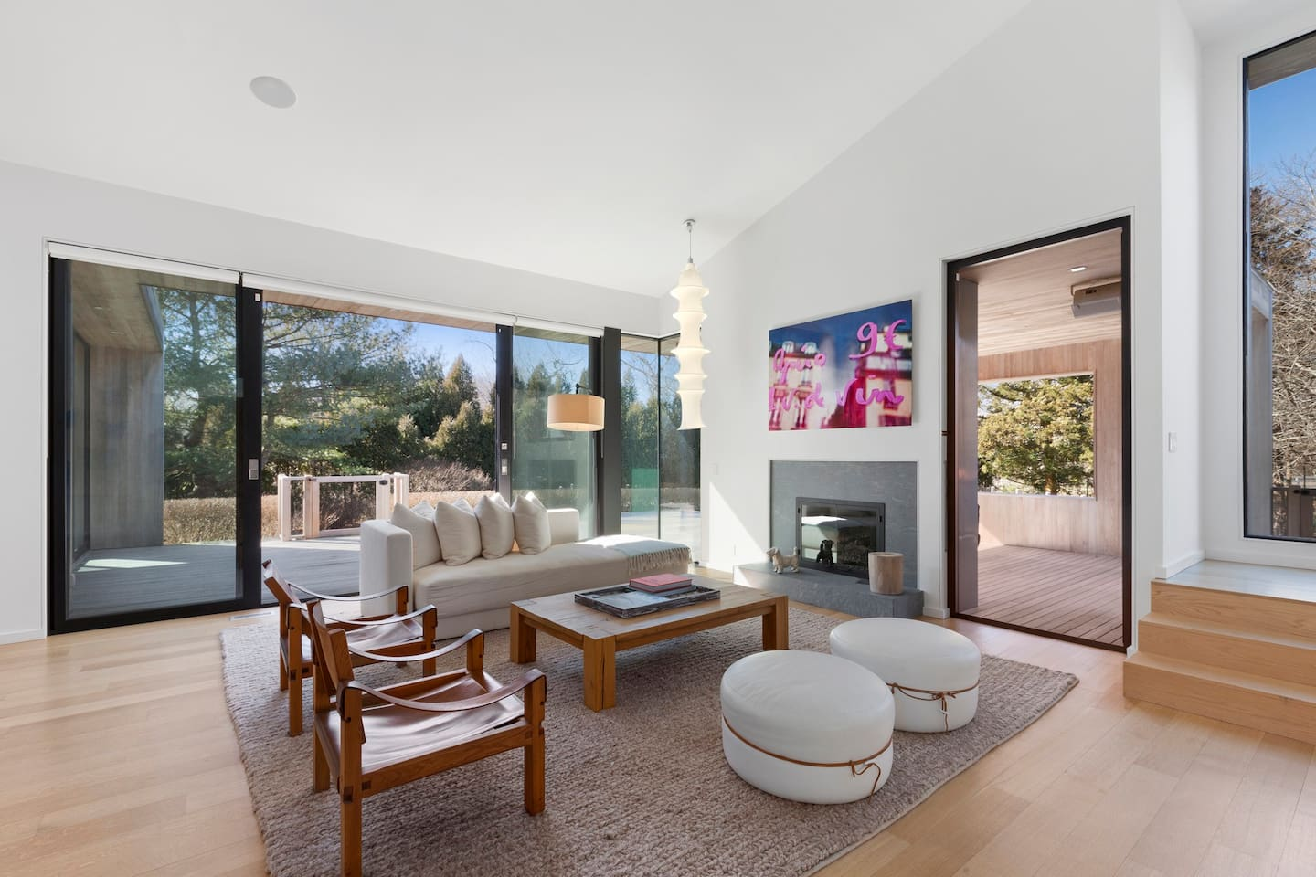 """Living Room """"Outdoor Indoor Living"""" - full dining table outside as well as L-sofa, loungers and outdoor fireplace on covered deck."""