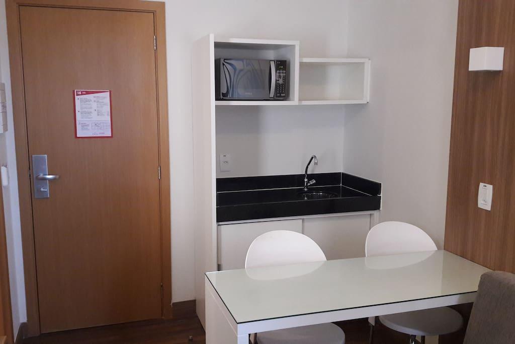Cozinha com microondas. O frigobar está localizado em baixo da TV