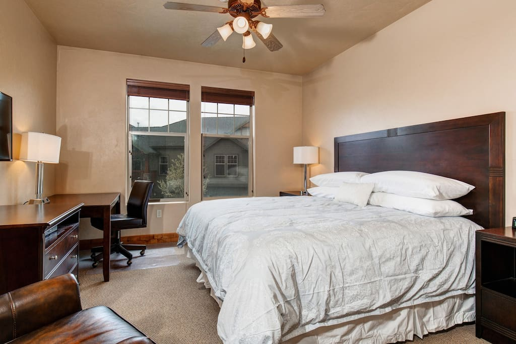 The master bedroom boasts a king bed with cherry wood headboard and fine linens.