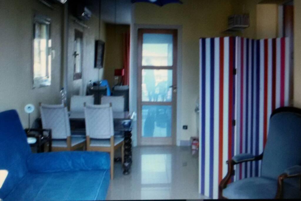 Un canapé lit, un coin salle à manger et derrière le paravent :cuisinière électrique, four, évier, placard. ..