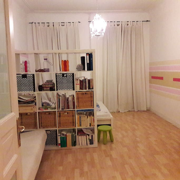 Schlafzimmer mit Schlafcouch, großem Bett und Raumteiler.