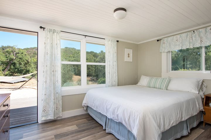 Back cottage California King bedroom with views of the valley. Your own private entrance leads to the back deck and seating area where you may access the attached game room or walk along the flagstone path to the main house.