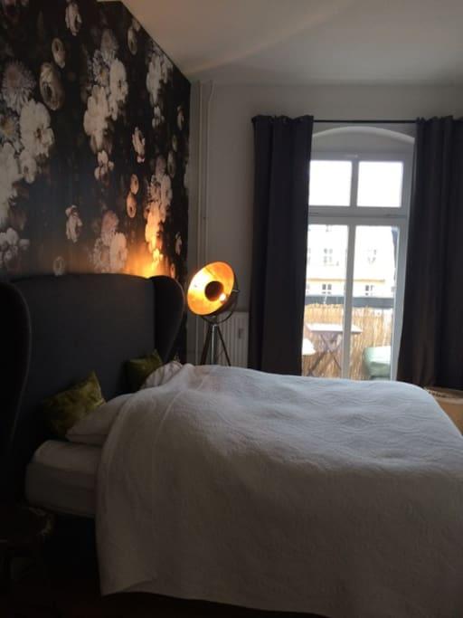 Schlafzimmer mit 180cm Bett und Zugang zu einem Balkon mit Blick auf den Alex