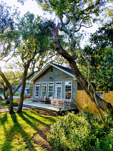 The cottage is nestled under a canopy of live oak trees.