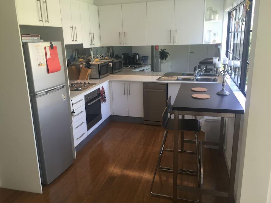 Kitchen with modern fridge, gas stove and dishwasher