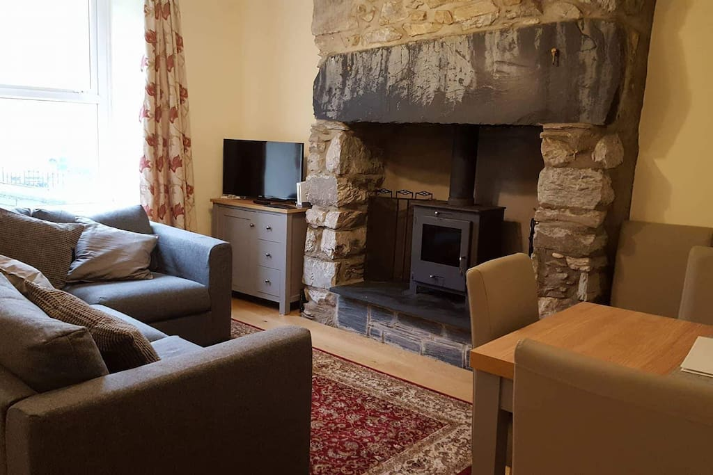 The living room, showing the sofa, TV cabinet and smart TV (satellite and internet), wood-burning stove and dining table (not extended)