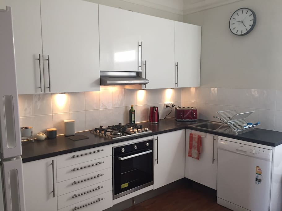 Kitchen contains new appliances, coffee pod machine with pods, dishwasher and washing machine.