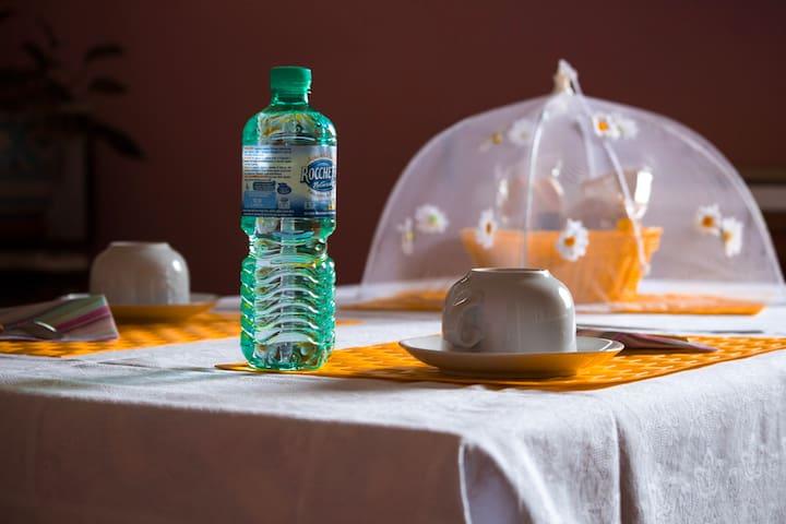 Il tavolo con la colazione. per ogni notte di pernottamento forniamo una bottiglietta d'acqua per ospite.