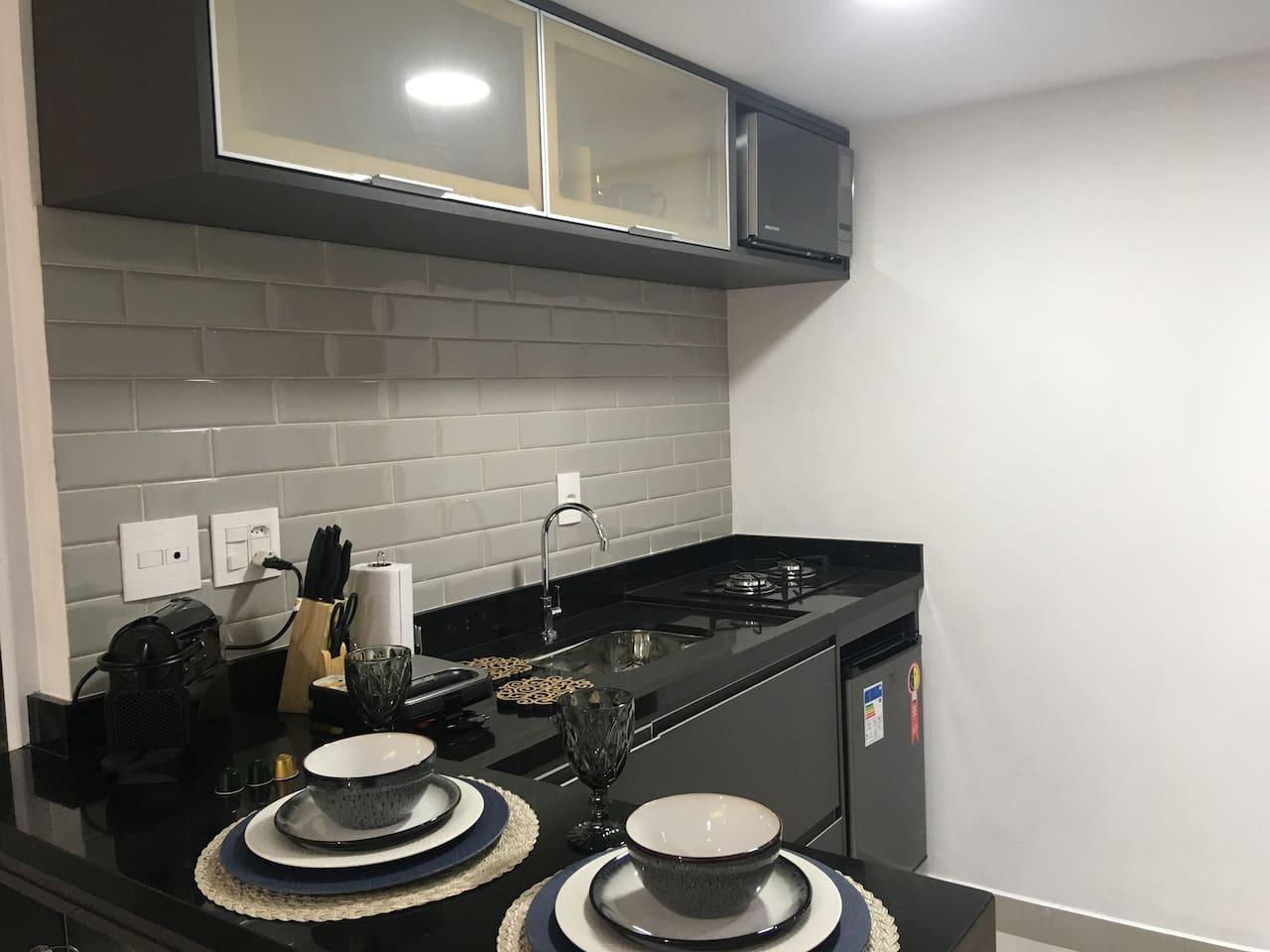 Cozinha compacta com frigobar, micro-ondas, cafeteira Nespresso, Sanduicheira e utensílios tudo novos.