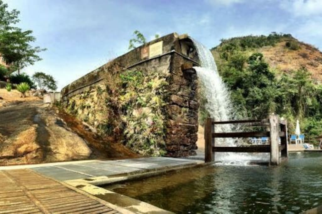 Lateral da piscina natural com cachoeira e área de deck exclusiva para hóspedes.