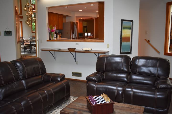 """Family room  with wood pellet stove and 65"""" TV."""