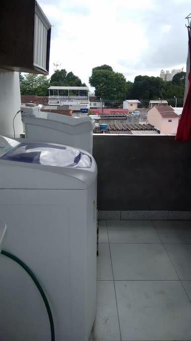 Lavanderia no terceiro andar com máquina de lavar e varal.