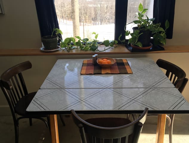 Dining table or breakfast nook, with an eastward view out over the woods and mountains of New Hampshire.