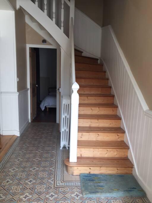 L'entrée  avec escalier menant au 1er étage. au fond un chambre pour adultes