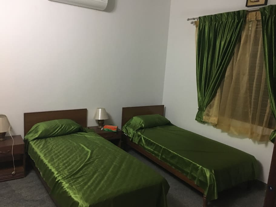 The olive room . Two single beds that can be joined ,attached bathroom and a teak wardrobe.the room has both a fan and an air conditioner.