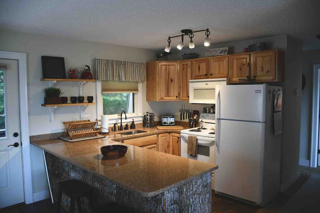 Full kitchen with island wrapped in tree bark design.