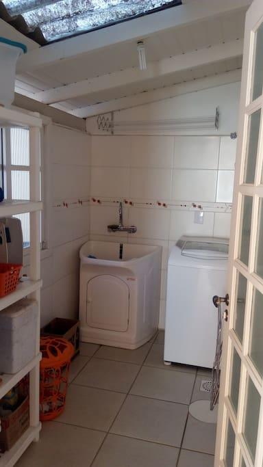 Lavanderia com tanque e naquina de lavar. Casa com varal na area externa.