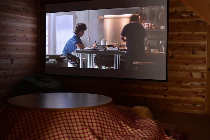 スクリーンで映画や動画もみれます。冬はコタツがお出迎え!