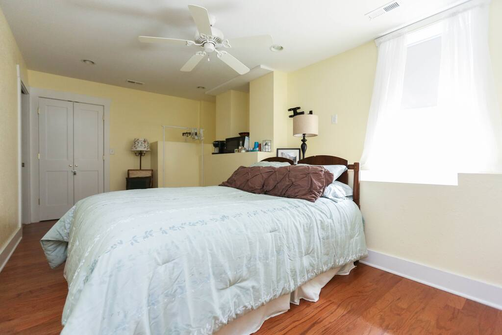 Master Bedroom - comfy queen bed, rocking chair, coffee maker, microwave, dresser, clothes rack, iron, ironing board