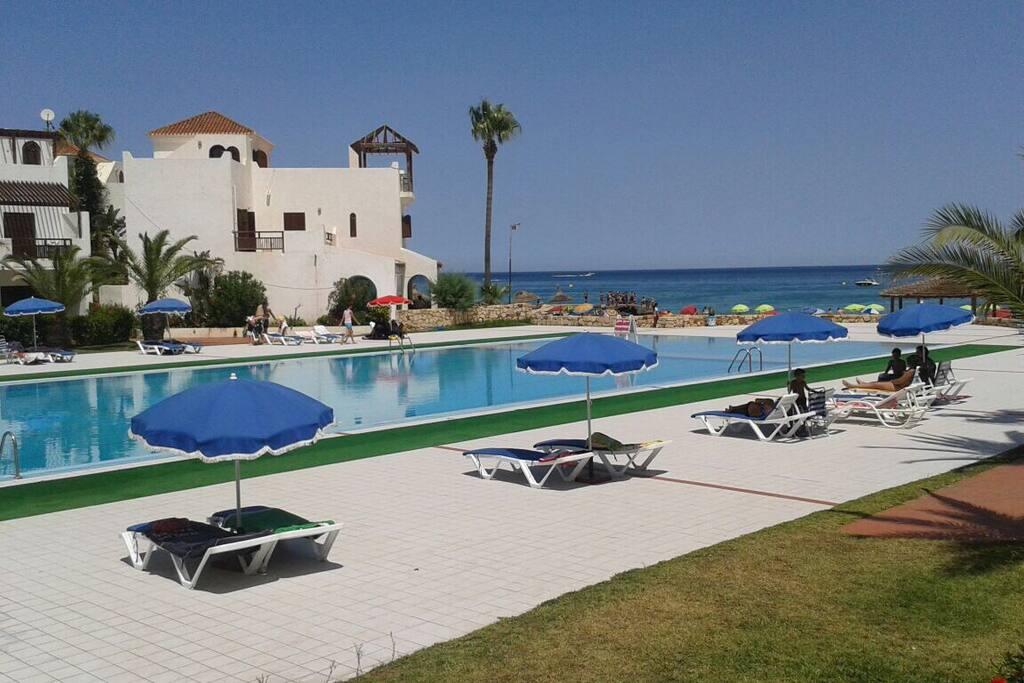 Grande piscine avec transat et parasols