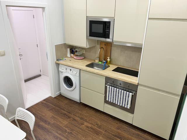 Here you have the kitchen and washing machine. Washer, stove, oven, microwave, and refrigerator. In the cabinets, we have plates, bowls, glasses, and mugs. In the drawers, you have cutlery and pots and a pan. Kitchen towel. You also see the entrance.