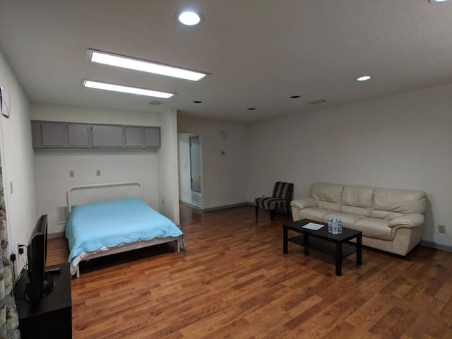 Living room with full size bed, TV, couch and coffee table