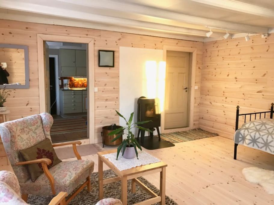 Bedroom / sitting room. The room is light and airy, pine clad, with an electric heater and a wood burning stove.